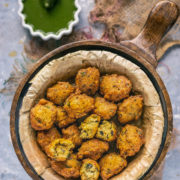 Crispy Moong Dal Pakora served n a round bowl with green chutney on the side