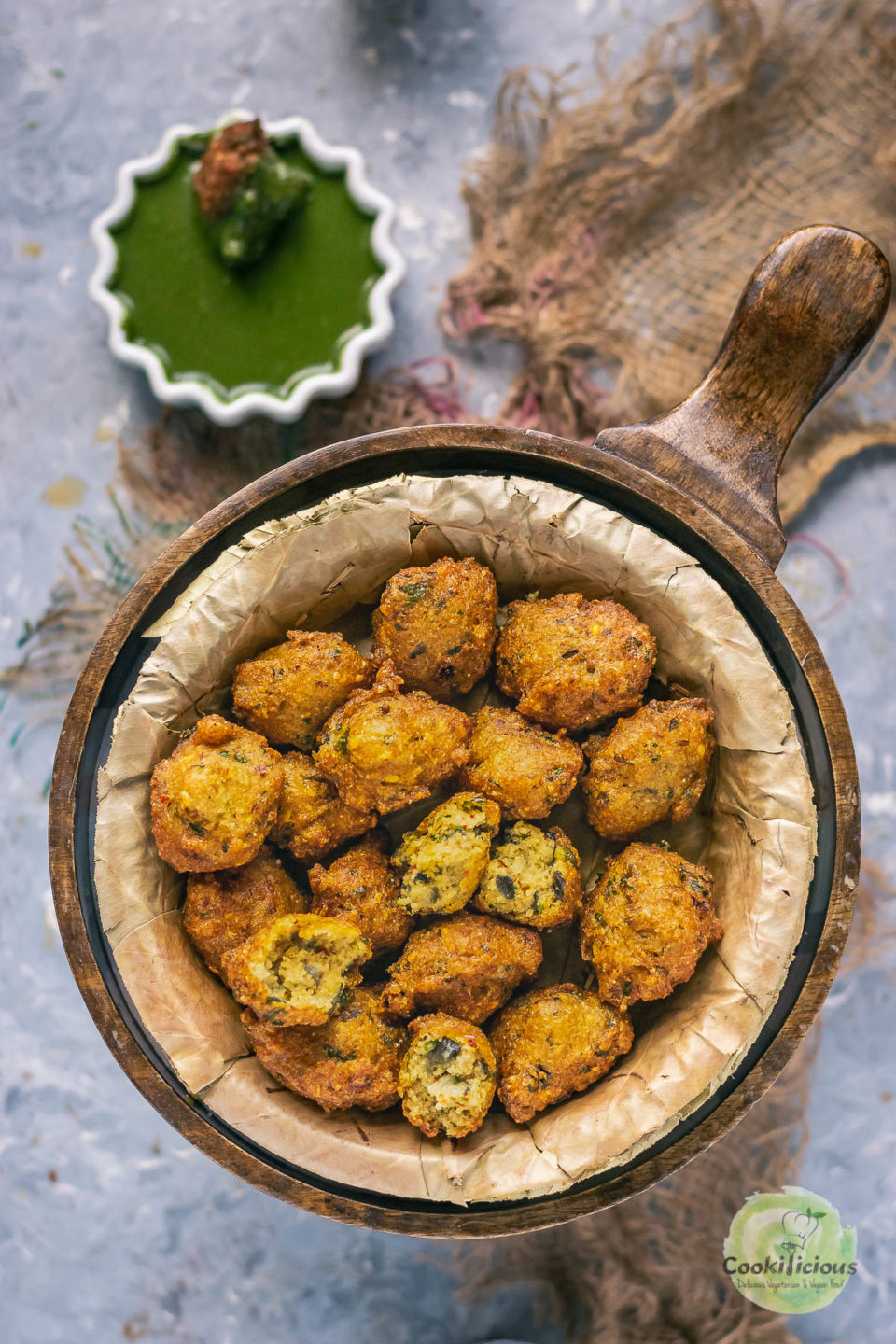 Crispy Moong Dal Pakora (one of the popular easy vegan appetizers) served n a round bowl with green chutney on the side
