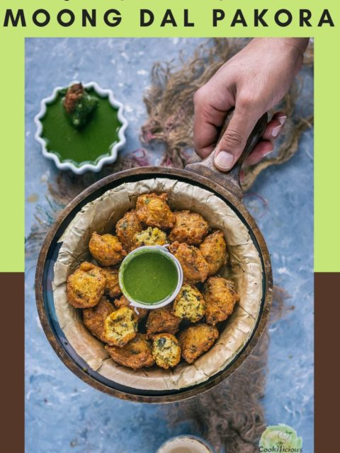 a hand holding a serving platter which has a bowl of Crispy Moong Dal Pakora and a bowl of green chutney next to it and text at the top