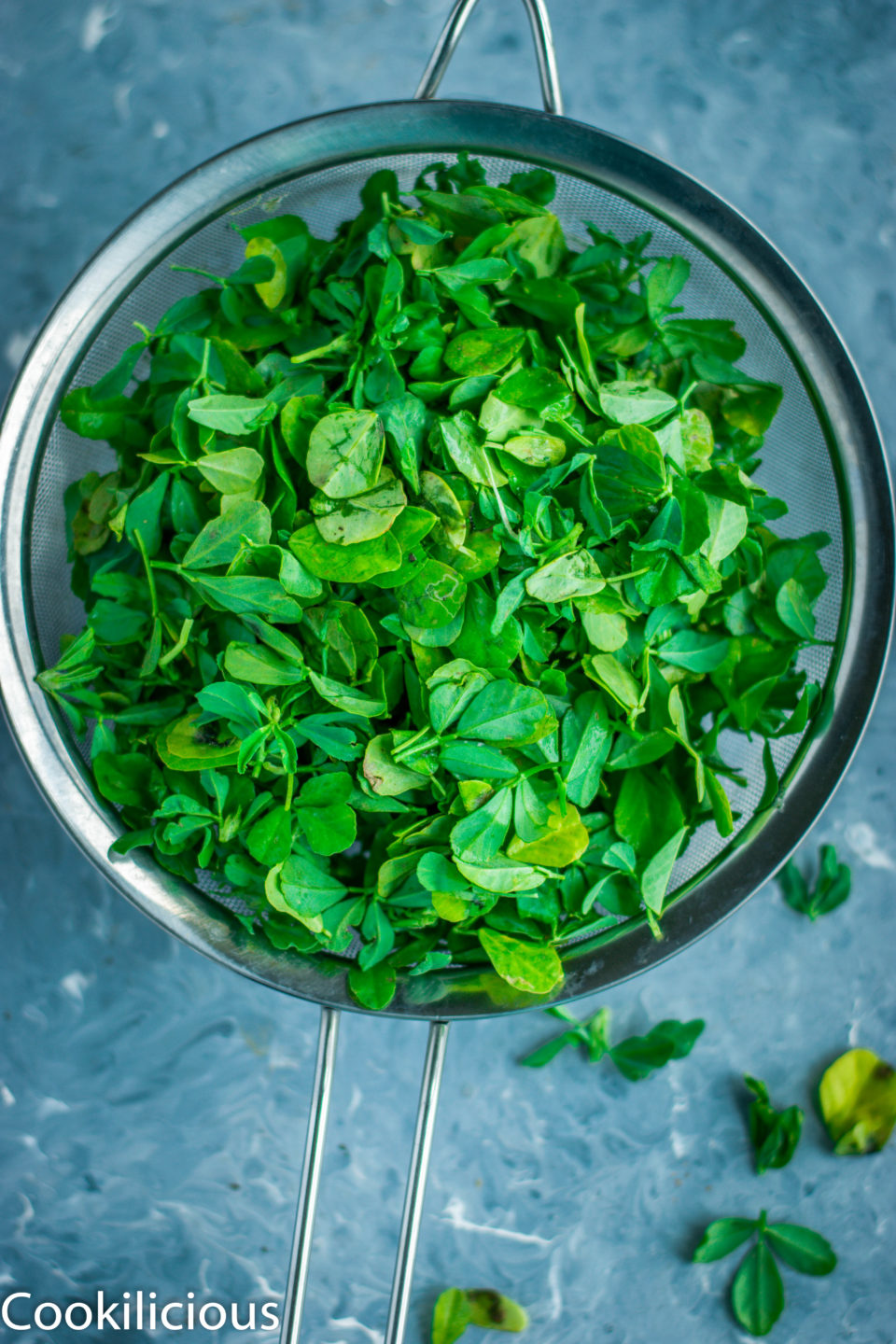 methi leaves in a strainer being used to make Methi Matar Malai