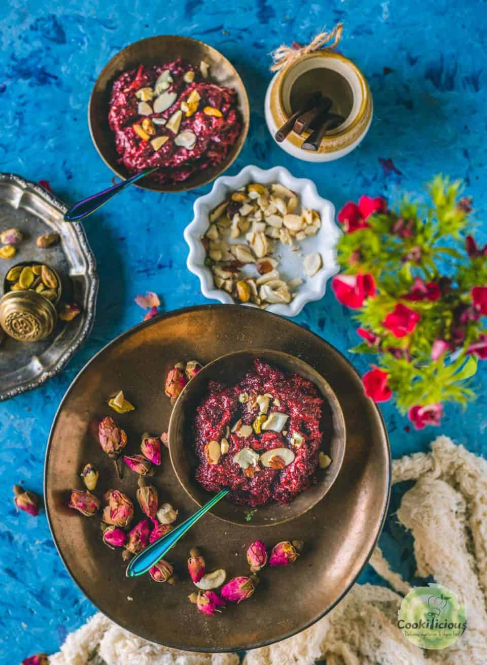 one bowl of Beetroot Halwa served in a round plate with rose buds around it while the other bowl is next to it