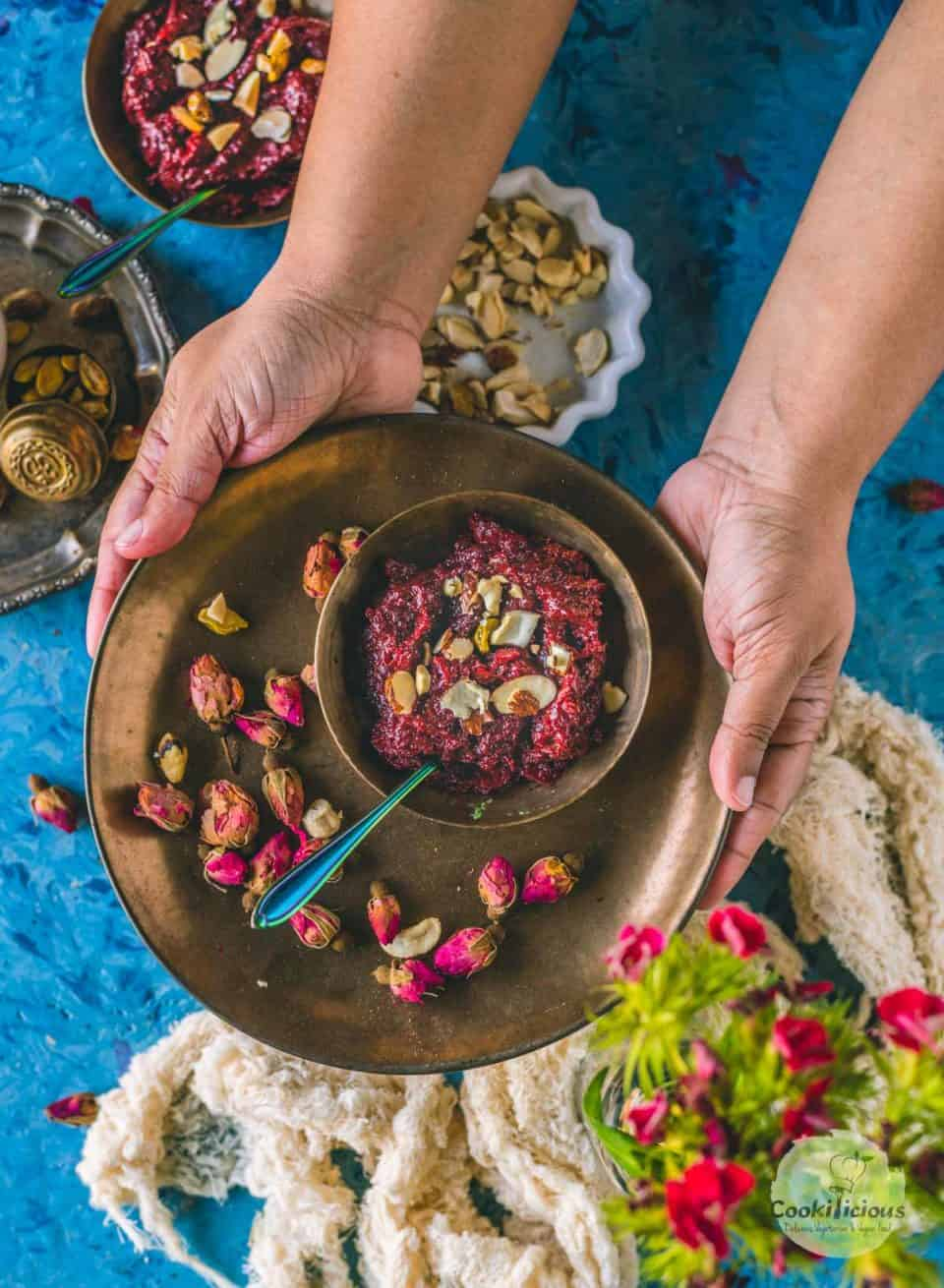 a set of hands serving a bowl of Beetroot Halwa