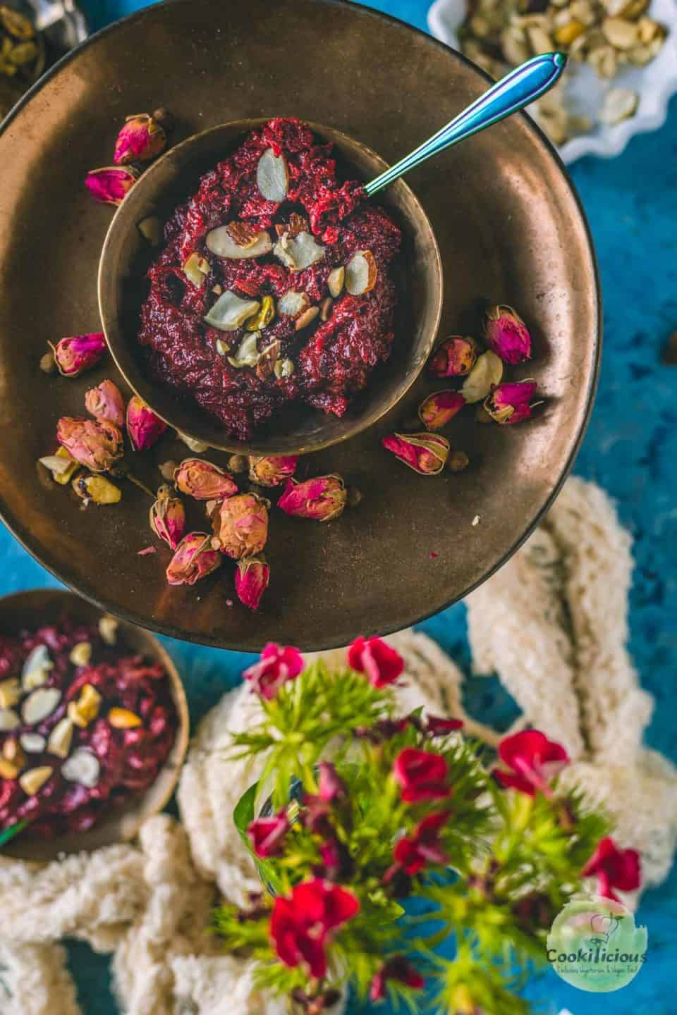 A bowl of beetroot halwa served with a spoon in it