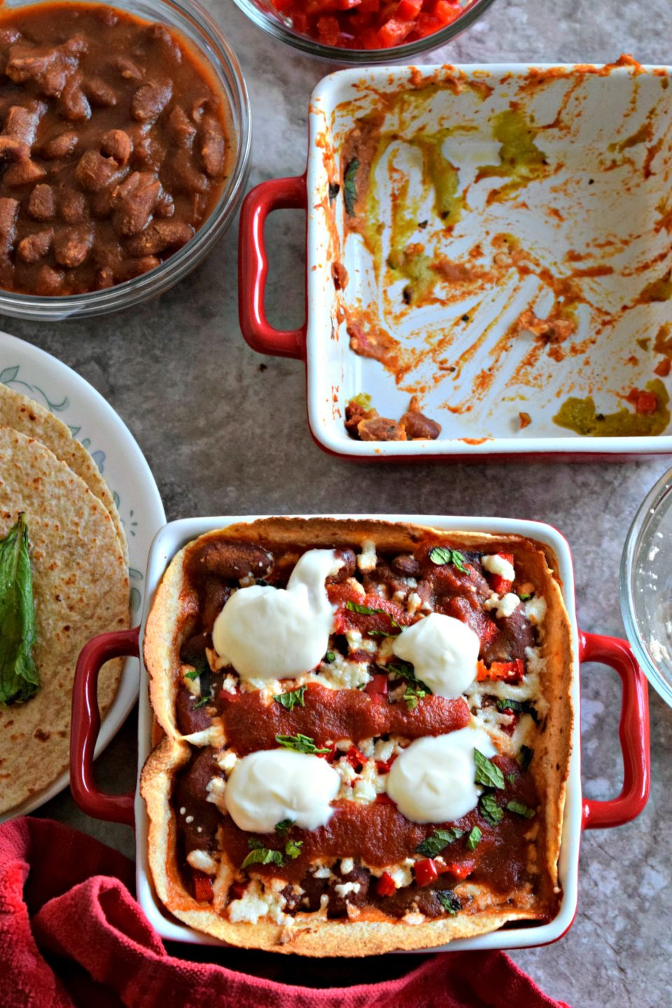 one empty casserole next to a casserole of Vegan Enchilada With Beans