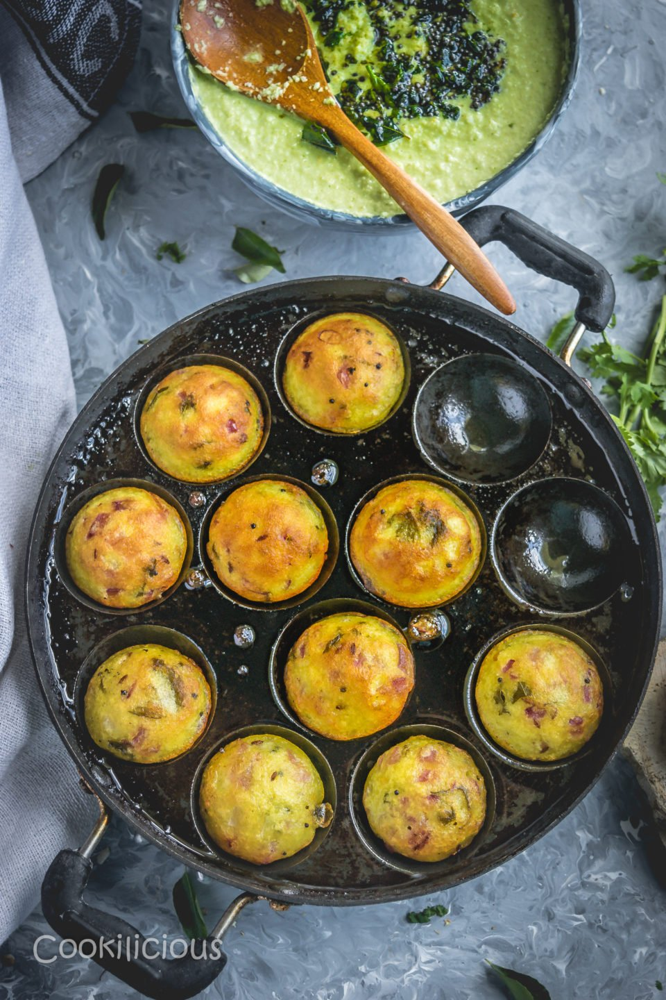 flat lay image of an appe pan with Chettinad Kuzhi Paniyaram in it besides a bowl of green chutney