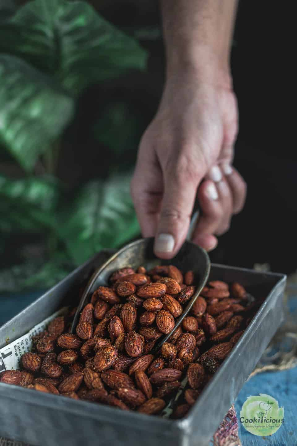 A hand using a scoop to get some Smoky Spicy Garlic Roasted Almonds from the platter
