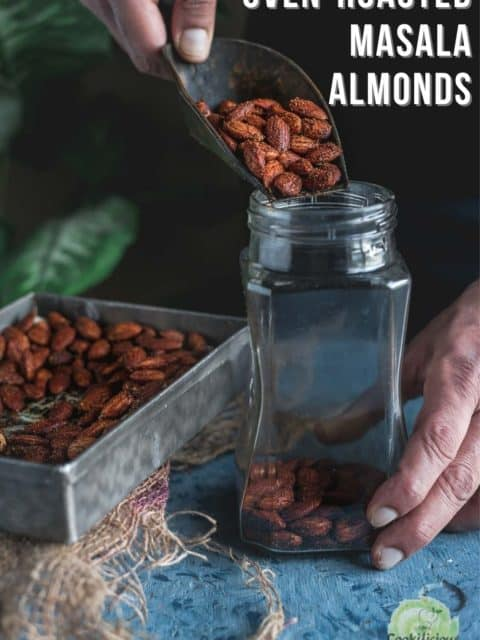 a hand pouring some Smoky Spicy Garlic Roasted Almonds into a glass jar and text at the top right