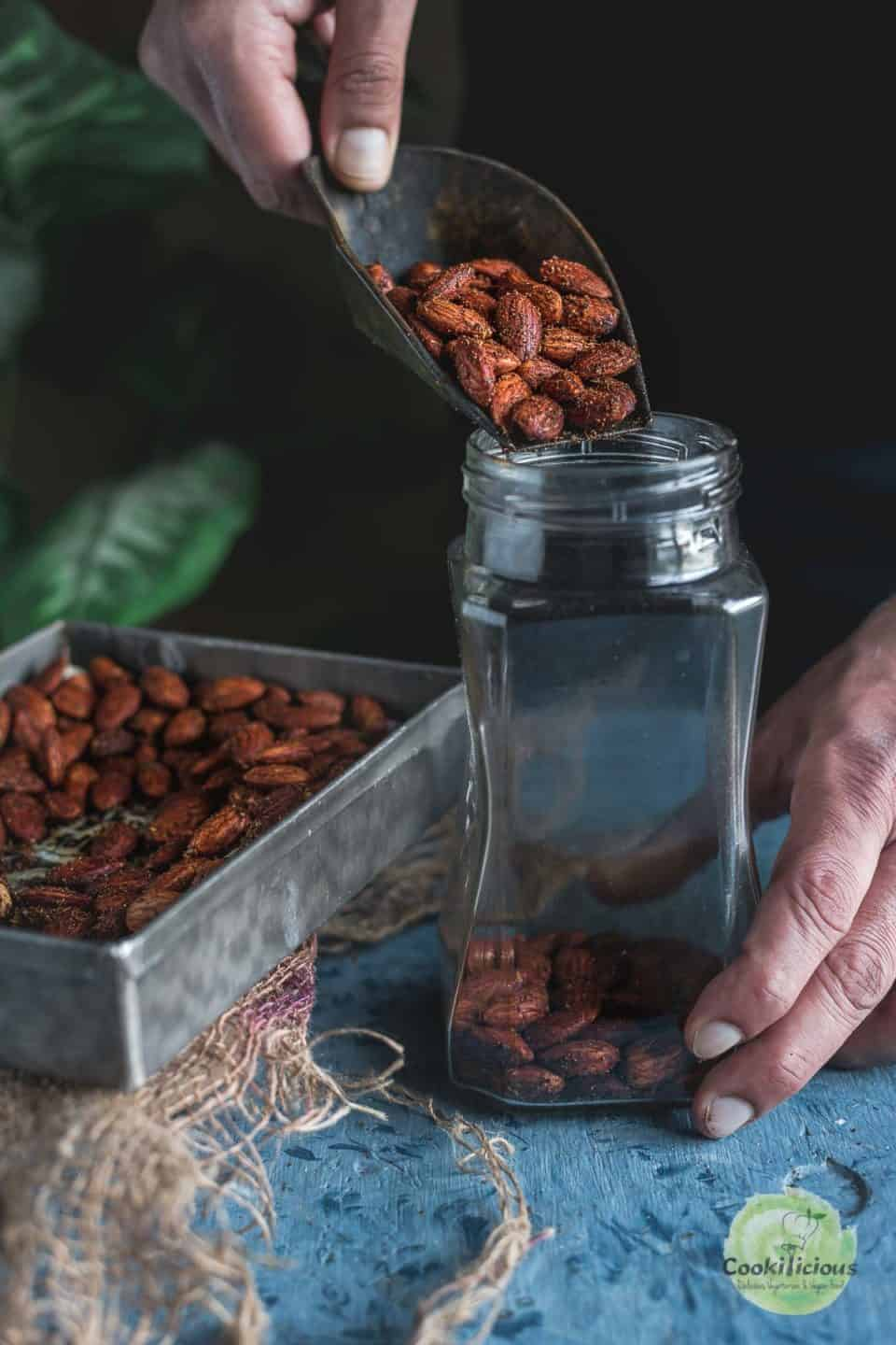 a hand pouring some Smoky Spicy Garlic Roasted Almonds into a glass jar