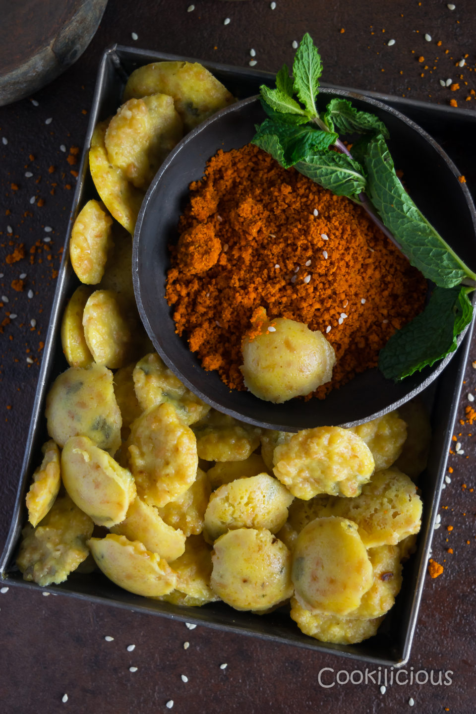 A square tin filled with mini idli made of bulgur wheat & sweet corn, served with red peanut chutney and garnished with mint leaves