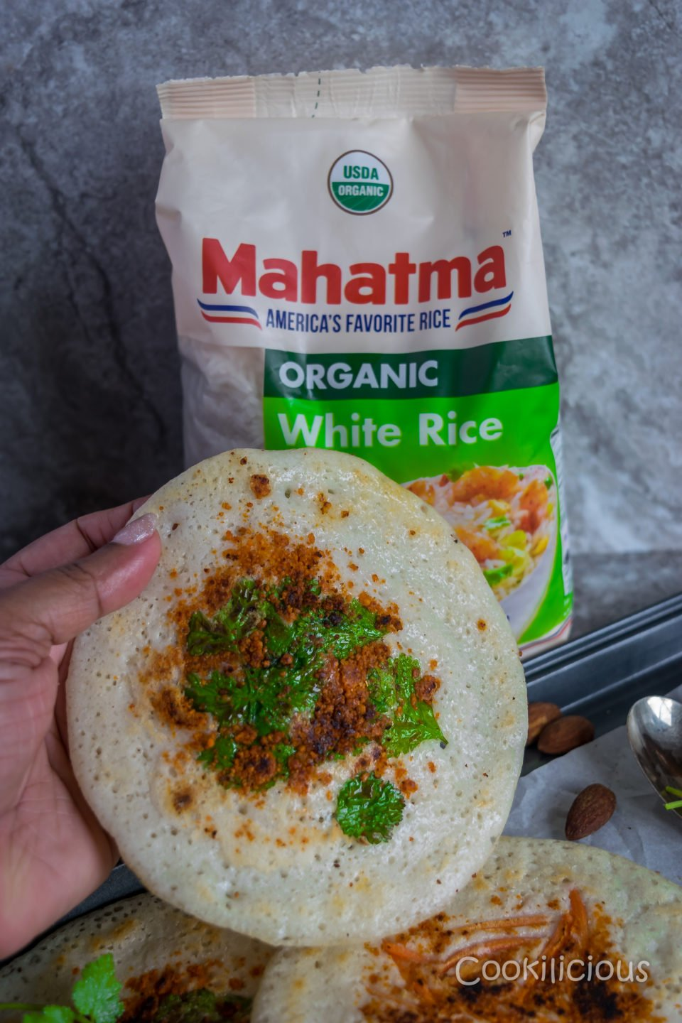 A hand holding an uttapam made from dosa batter with Mahatma Organic white rice bag in the background