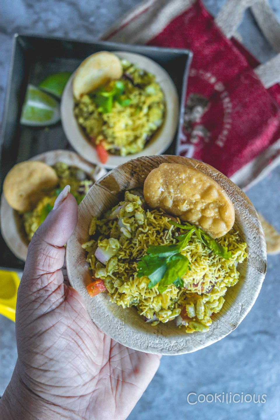 a close up shot of a hand holding a bowl of bhelpuri
