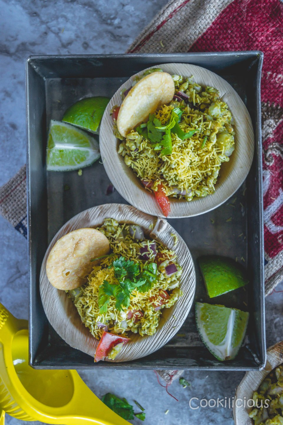 A tray with 2 bowls of bhelpuri with lemon wedges around it
