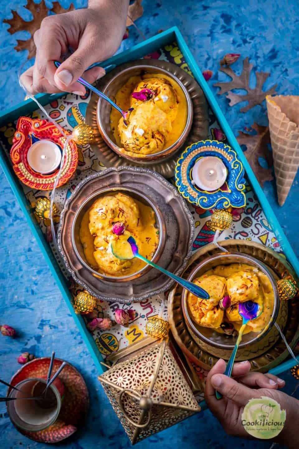 2 hands digging into two bowls of Carrot Halwa Ice Cream