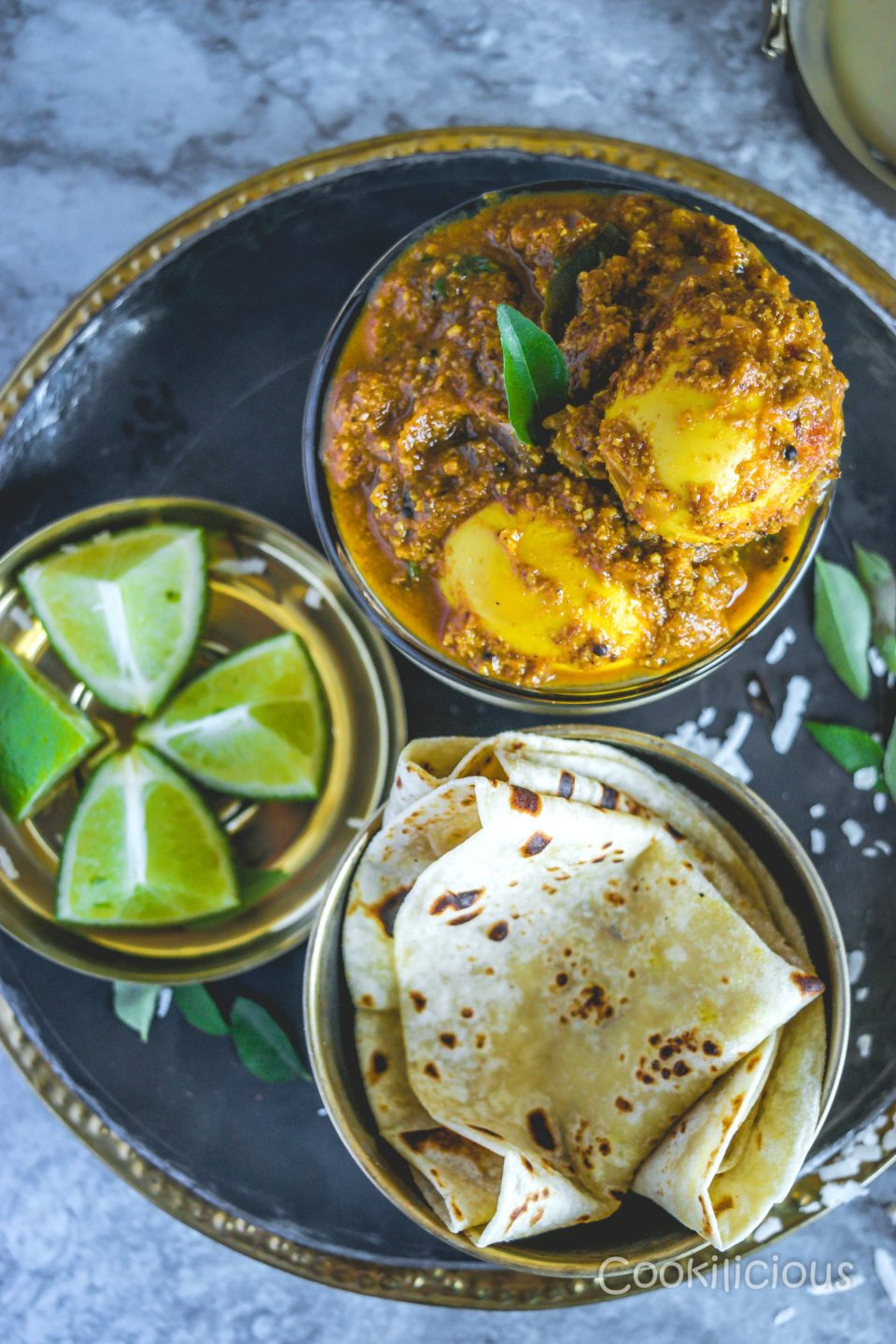 Flat lay shot of Spicy Chettinad Style Egg Roast Curry on a plate served with phulka and lemon wedges