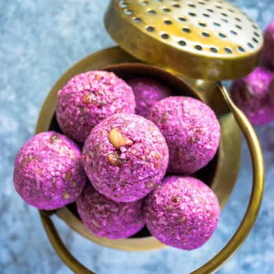 top shot of Frozen Raspberry Date Coconut Balls in a brass bowl