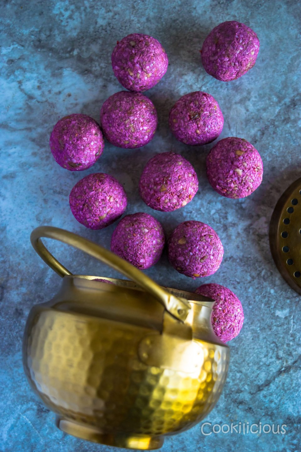 flat lay shot of Frozen Raspberry Date Coconut Balls fallen from a brass bowl