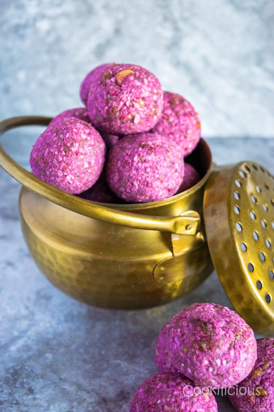 A brass bowl filled with Frozen Raspberry Date Coconut Balls
