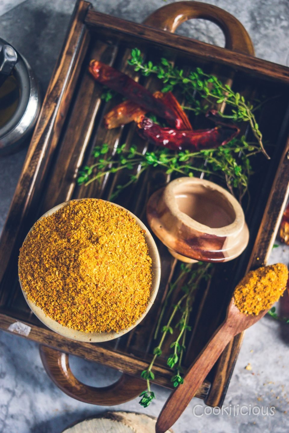 A wooden tray with a jar filled with sambhar powder with some thyme and red chillies besides it