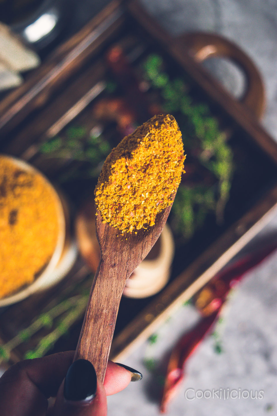 close up shot of a wooden spoon filled with sambhar powder