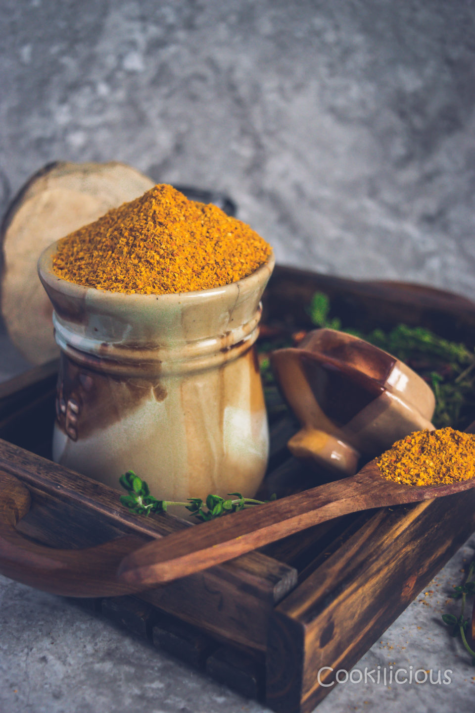 side shot of a jar and wooden spoon with sambhar powder in a wooden tray