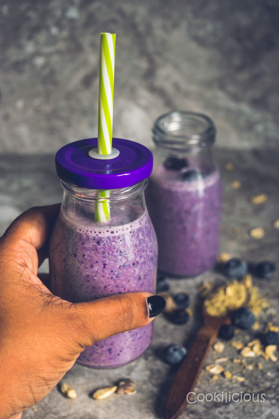 a hand holding a glass of Vegan Blueberry Pancake Almond Milk Smoothie