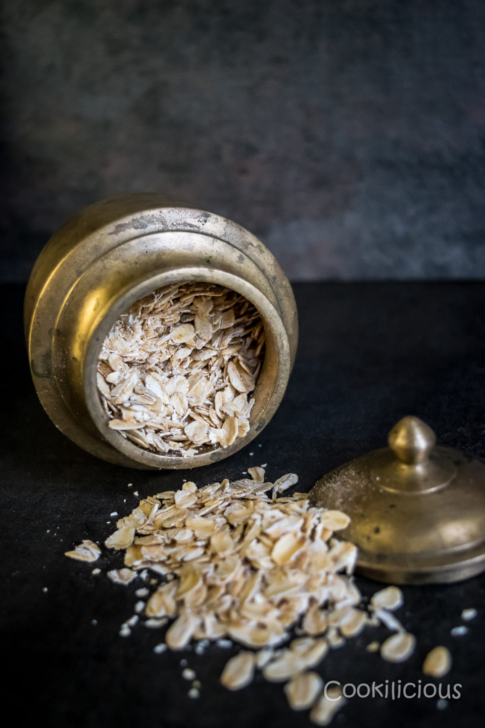 image of rolled oats falling off a brass container