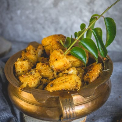 side shot of Crispy Raw Banana/Plantain Fry in a brass bowl