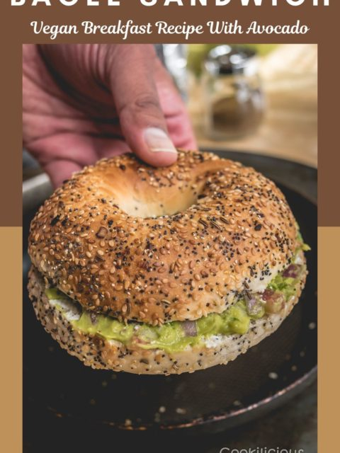 a hand holing one Breakfast Bagel Sandwich With Guacamole and text at the top