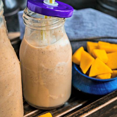 close up shot of one small bottle with Dairy Free Mango Figs & Apricot Power Smoothie and some chopped mangoes in the background