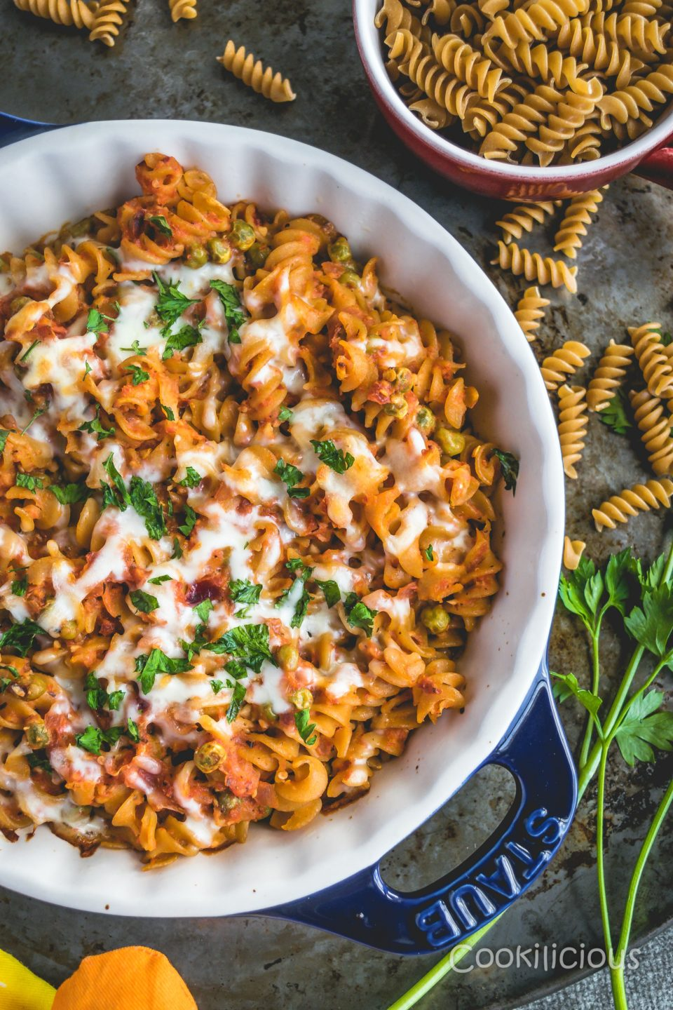 top shot of Easy Cheesy Tomato Rotini Pasta Bake with uncooked pasta in the background