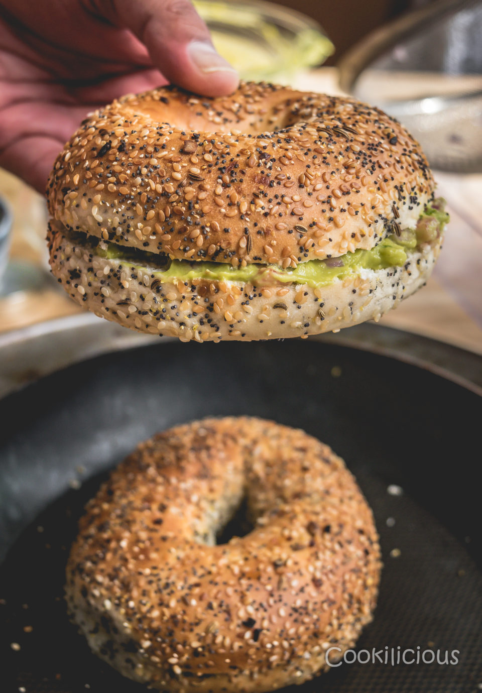 a hand lifting oneBreakfast Bagel Sandwich With Guacamole while the other rests below