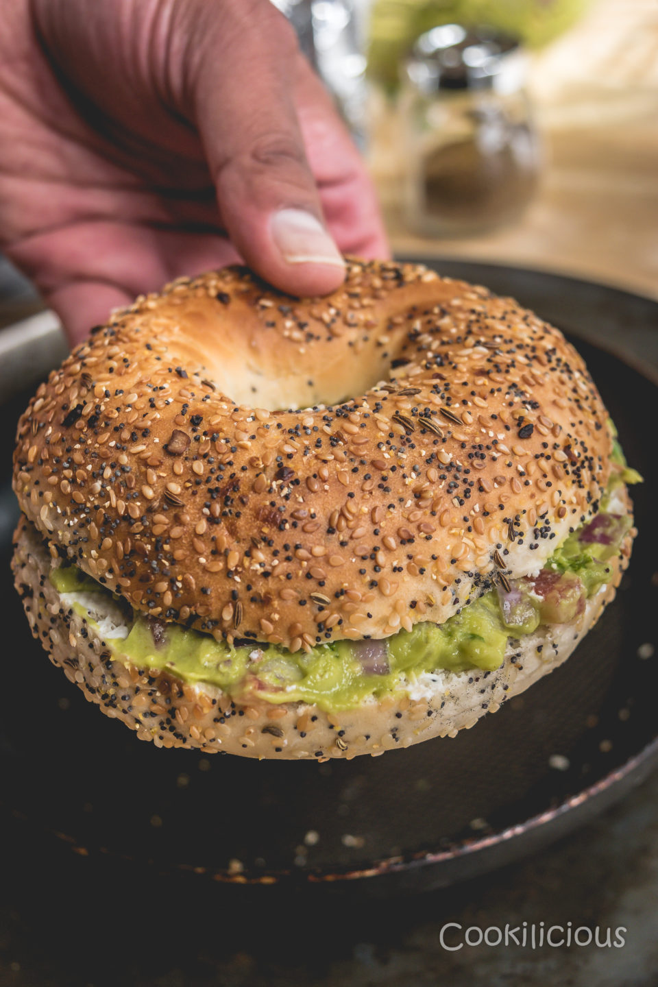 a hand holing one Breakfast Bagel Sandwich With Guacamole