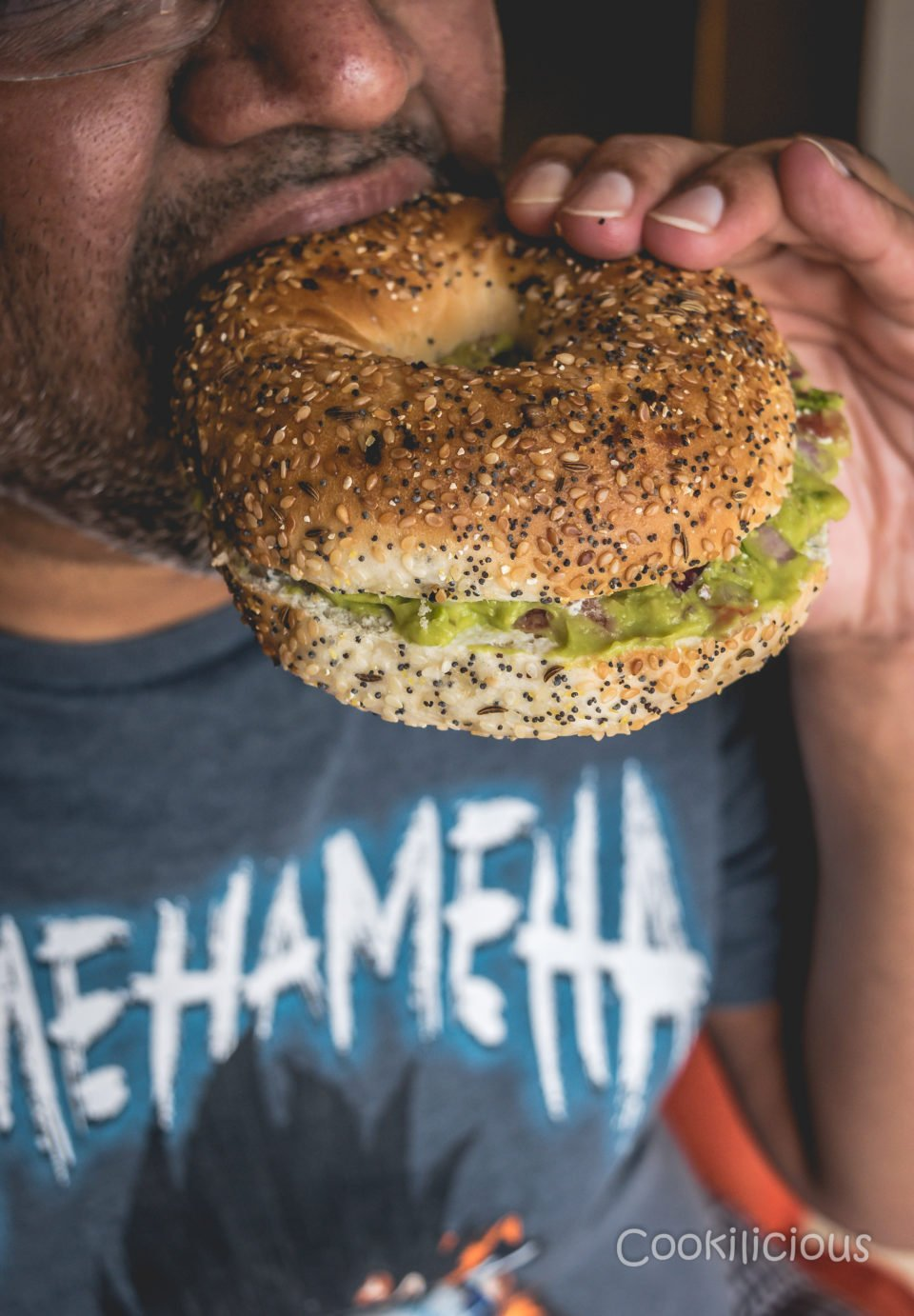 a man eating Breakfast Bagel Sandwich With Guacamole
