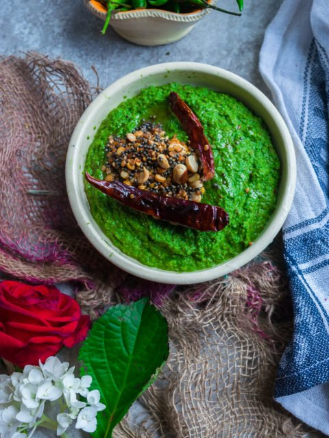 Flat lay image of a bowl of Vegan Spinach & Peanut Chutney with tadka on top with a rose, kitchen towel and a bowl of green chillies around it