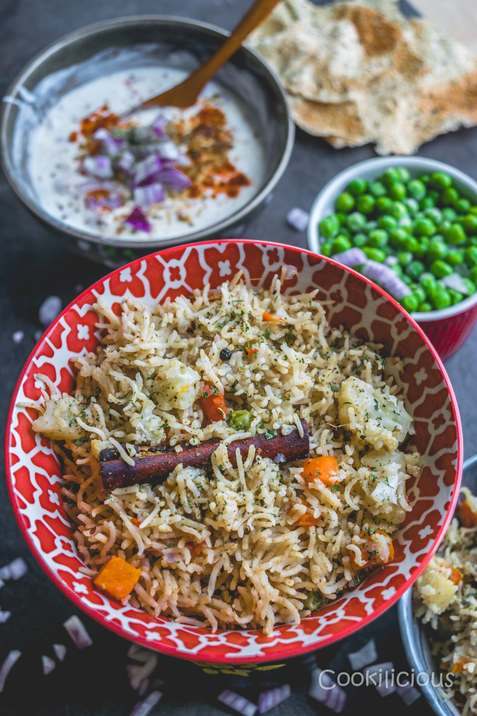 A bowl of Vegetable Pulao in an Instant Pot with raita and green peas in the background