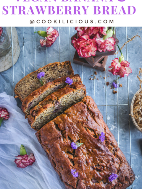 flat lay image of Banana & Strawberry Bread where half of it is cut in slices and flowers around it with text on top