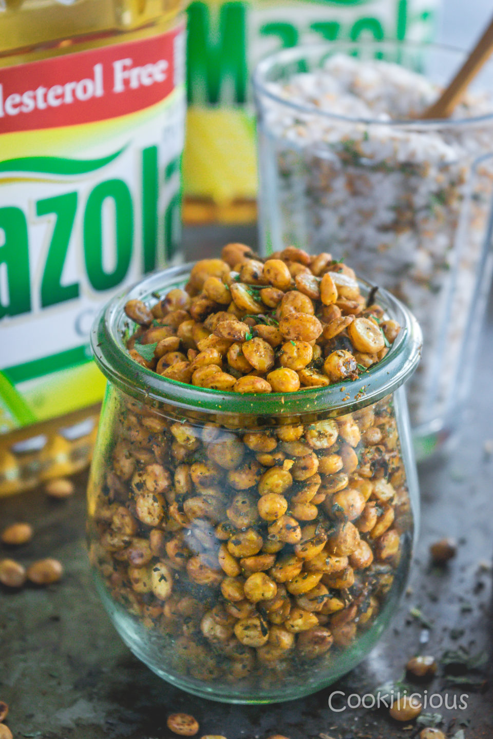 front shot of a jar filed with Crispy Vegan Split Peas with Mazola corn oil bottle in the background