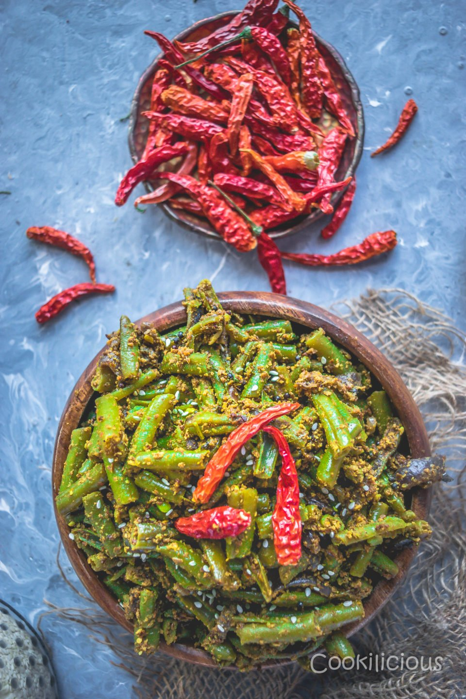 top angle shot of a bowl filled with Sesame Flavored Green Beans Stir Fry and dried red chillies on the side