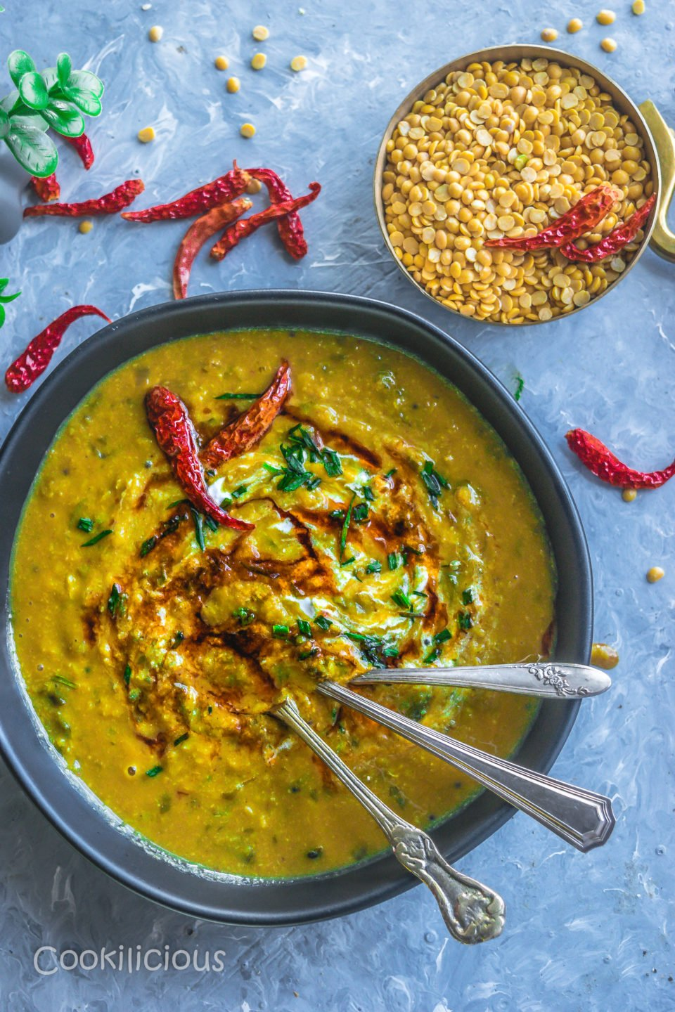 a ceramic bowl filled with Malvani Style Tikhat Dal with 3 spoons in it and a bowl of dry lentils besides it