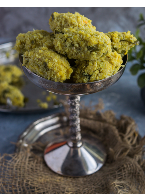 a tall glass holding Spicy Steamed Lentil Balls with text on top