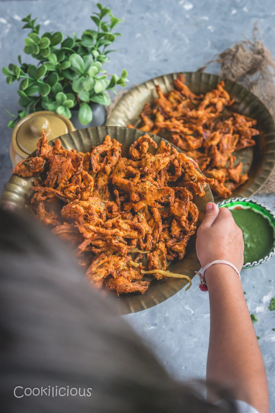 a little girl holding a plate filled with Vegan Crispy Onion Pakoda | Fried Kanda Bhajiya