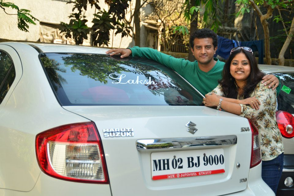 image of brother and sister standing by a car
