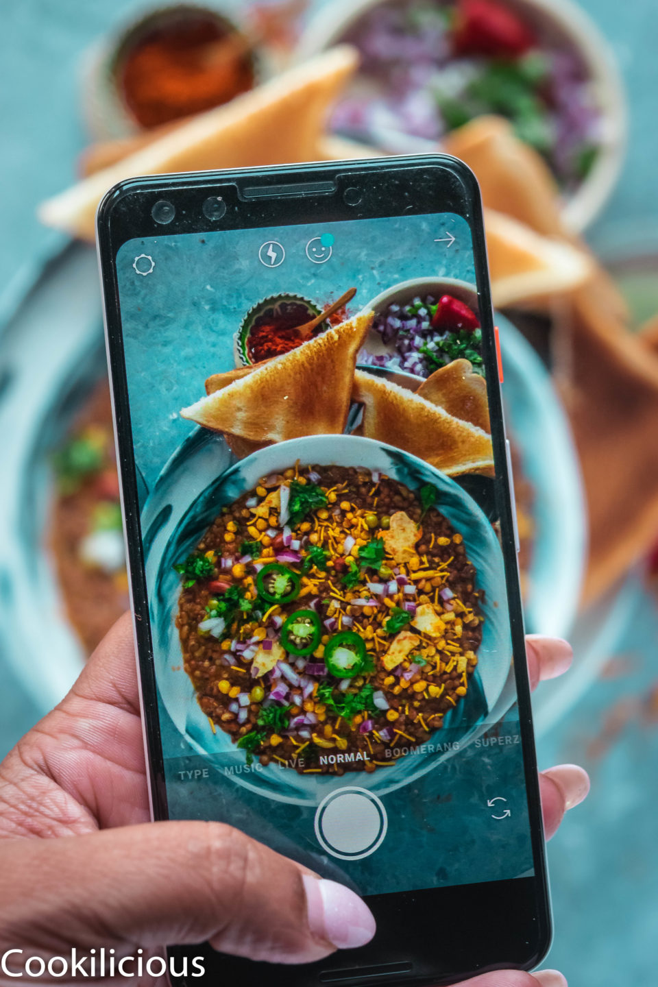 a phone clicking an image of a bowl full of Vegan Matki Misal