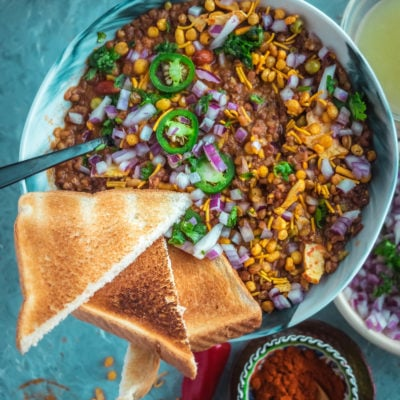 top angle close up shot of a bowl filled with Vegan Matki Misal with bread slices around it