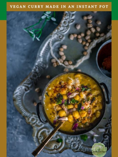 Instant Pot Potato Chickpeas Vegan Curry served in a bowl with a spoon in it placed over a tray and text at the top