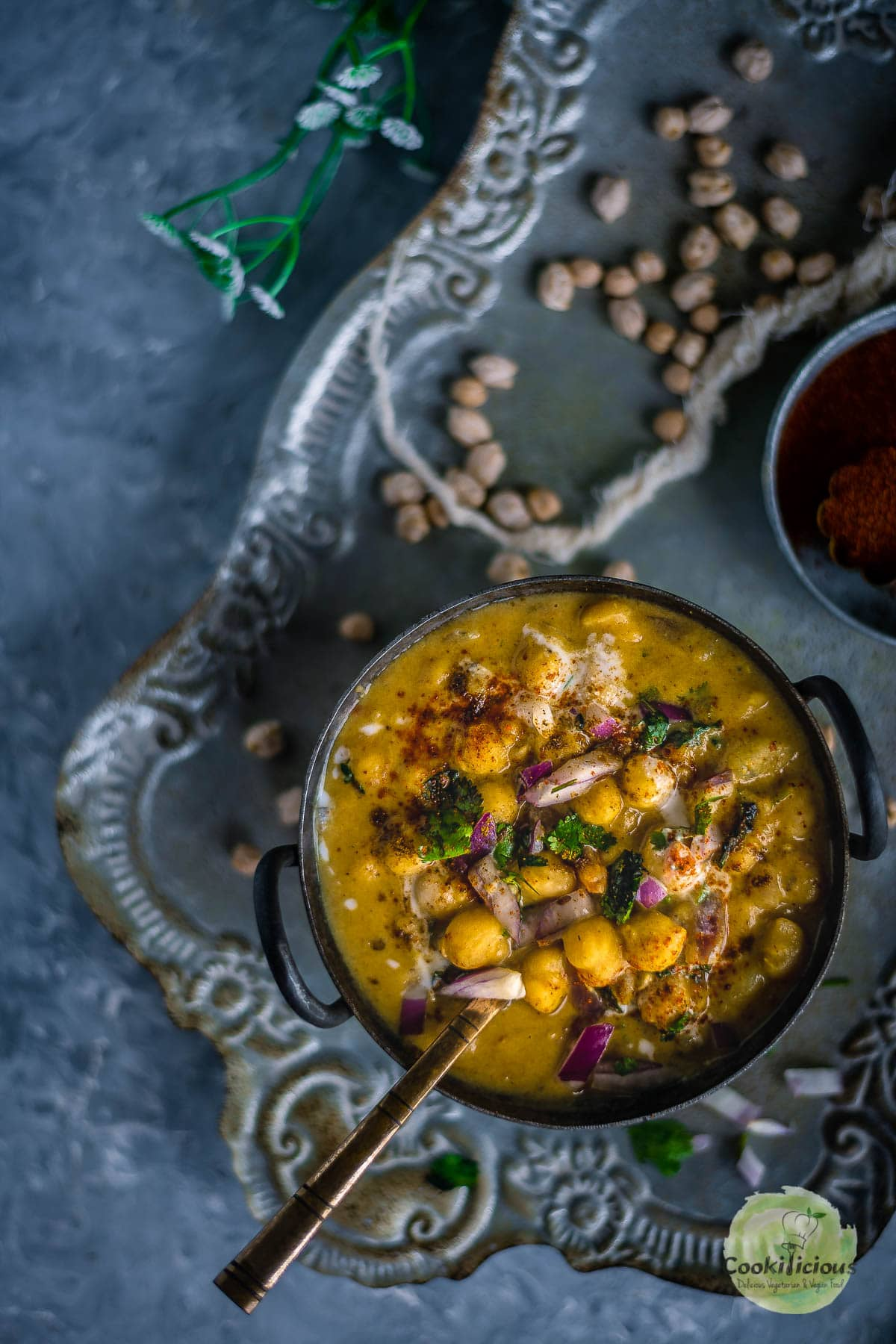 Instant Pot Potato Chickpeas Vegan Curry served in a bowl with a spoon in it placed over a tray