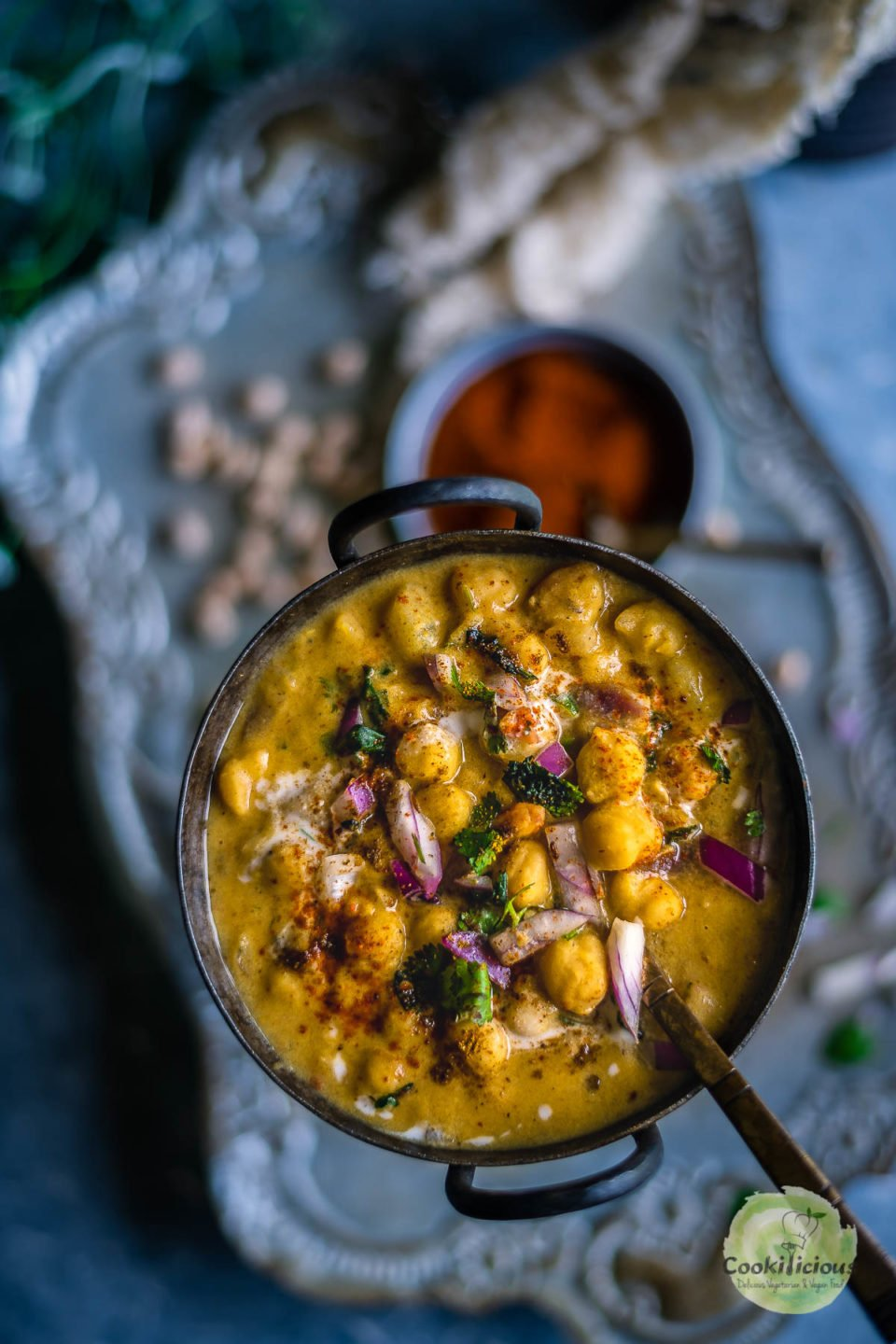 Instant Pot Potato Chickpeas Vegan Curry in a round bowl with a spoon in it