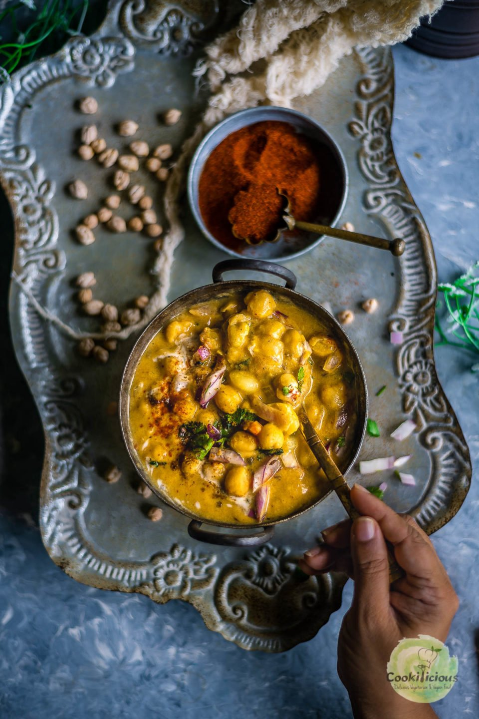 a hand holding a spoon and digging into a bowl filled with Instant Pot Potato Chickpeas Vegan Curry