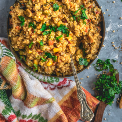 a round bowl filled with Instant Pot Oats & Vegetable Upma and a spoon in it