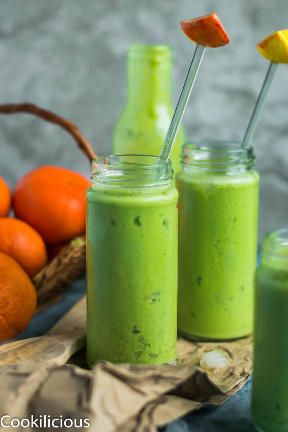 2 glasses of Super Healthy Mango Spinach Yogurt Power Smoothie with a stirrer in each